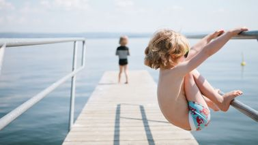 Kid travelling on a budget family vacation hangs off a pier