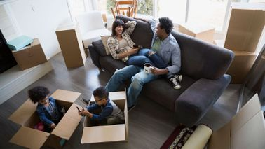 Family surrounded by moving boxes talking about furnishing a new home