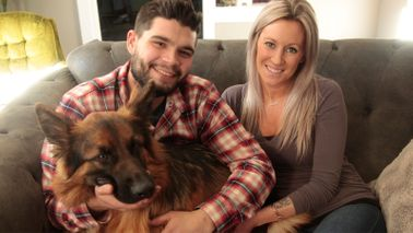 Couple and their dog relax on sofa after buying a house