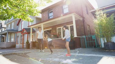 Family playing outside before refinancing their home