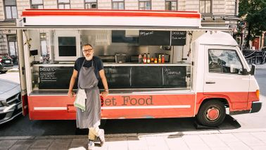 Man in front of food truck happy with his side job