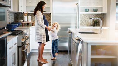 Achieving a better work-life balance mother playing with daughter in kitchen