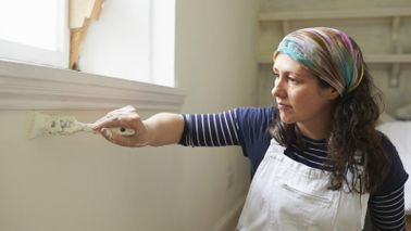 Woman painting with brush doing home improvement project