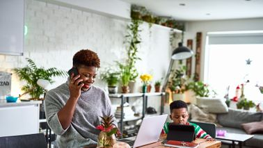 A woman working from home for the first time with her son