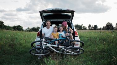 family unloading car trunk to go on bicycle ride