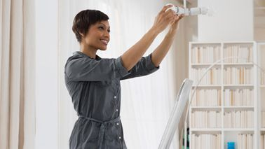woman changing a light bulb to maintain her home