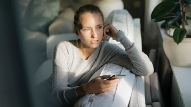 woman sitting on couch holding phone while gazing out the window