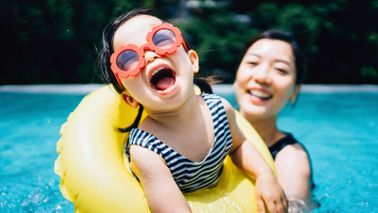 laughing girl with mom in pool in June