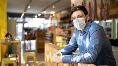 Male business owner and PPP loan recipient wearing a face mask