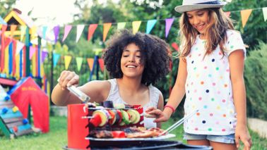 Mother and daughter barbecuing in backyard