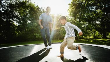 Father and young son jumping on trampoline