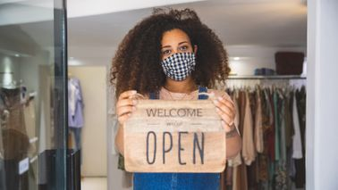 "woman holding ""Open"" sign in a small business"