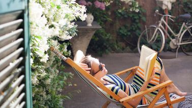 woman relaxing on deck chair in backyard reading