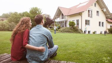 Couple watching kids play at new house after researching neighborhood online.