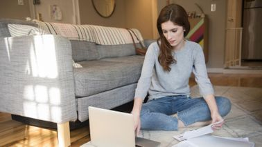 woman sitting on floor with open laptop paying student loans