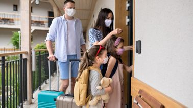 Family wearing face masks at hotel staycation