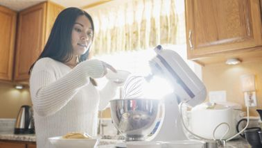 woman using stand mixer to make holiday treats