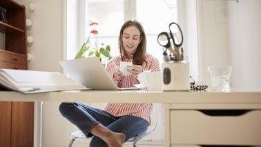 woman sitting at desk in home finding extra money in her budget at year-end