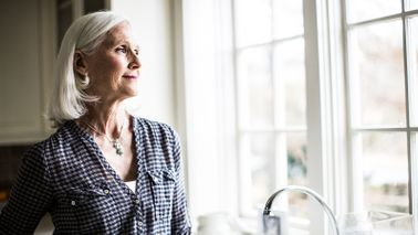 senior woman standing at kitchen sink looking out window