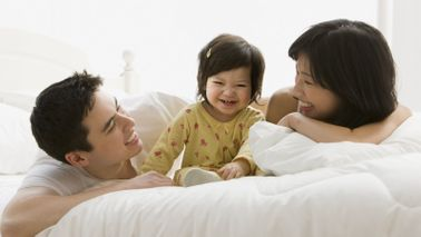Couple on a bed with their child after discussing how term life insurance works.