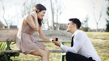 man proposing to woman in park with alternative engagement ring