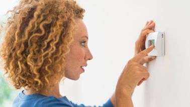 woman setting temperature on thermostat