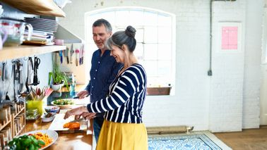A retired couple in the kitchen discussing the role of financial planning in retirement