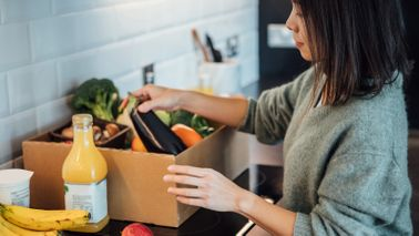 woman unpacking groceries at home