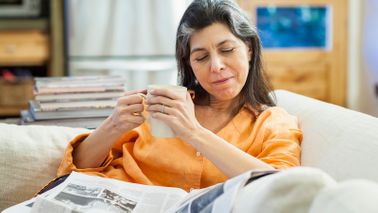 Woman reading newspaper about President Biden's coronavirus relief package