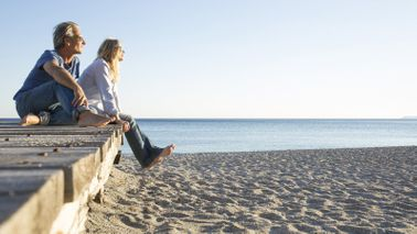 Couple sitting on a pier at a beach wondering how an annuity is taxed.