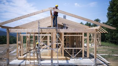 workers using lumber to construct the frame of a new home