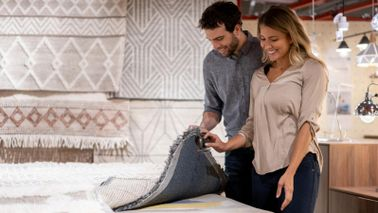 couple shopping for area rugs in July