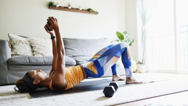 Woman exercising with weights at home