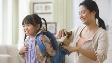 mom helping daughter get ready for school