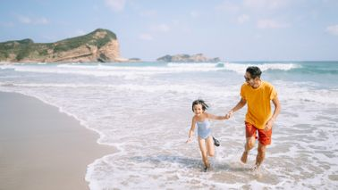 father and daughter playing in waves