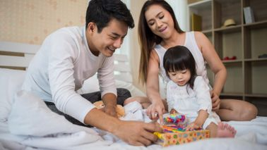 parents-with-child-tax-credits-playing-game-with-daughter-on-bed
