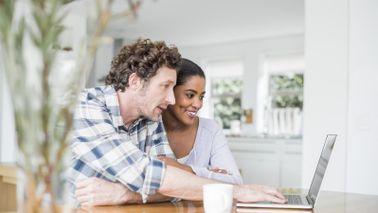 Couple checking their investment portfolio on laptop