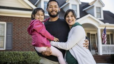 family in front of their home wondering about mortgage life insurance