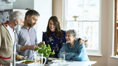 Adult kids making dinner for their parents wondering about life insurance for parents