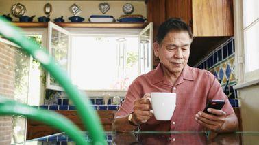 retired man drinking coffee in kitchen