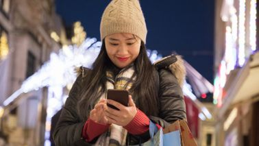 Woman checking her smartphone while doing holiday shopping