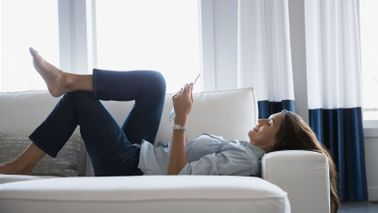 Woman relaxing on couch learning her financial health