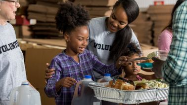 Mom and daughter volunteering teaching kids to be generous