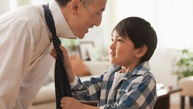Son adjusting his father's tie.