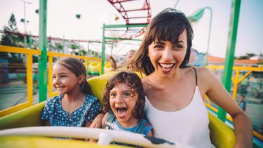 Mom and kids on a roller coaster after using family travel apps