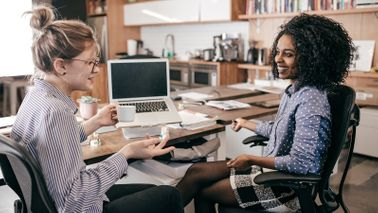 Two women talking in a networking space.