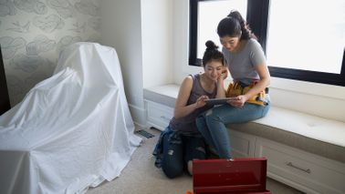 Mother and daughter work on a home DIY project.