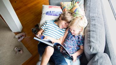 brother and sister reading on couch