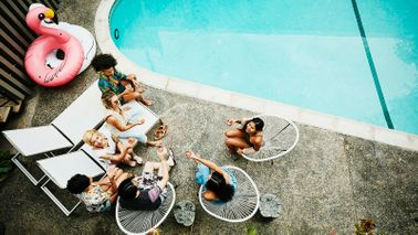 friends and family at a pool party in the backyard