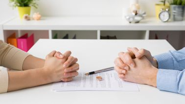 A man and woman negotiate their divorce at a table